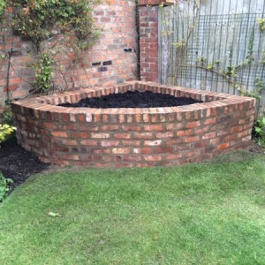 Corner raised bed in reclaimed bricks