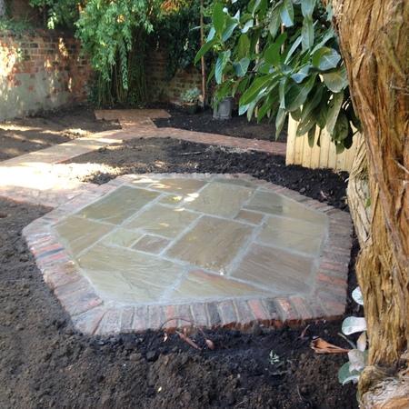 Hexagonal sandstone patio edged with reclaimed bricks