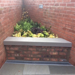 Corner raised bed with composite deck seating