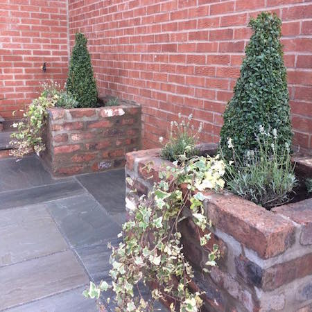 Reclaimed brick planters and grey sandstone paving